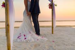 La novia y el novio debajo de la arcada en la playa Playa arenosa blanca tranquila y romántica para el destino de la luna de miel fotografía de archivo libre de regalías