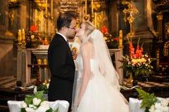 La novia y el novio del recién casado primero se besan en la ceremonia de boda en churc Fotos de archivo