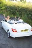 La novia y el novio Driving Away In adornaron el coche Imagen de archivo libre de regalías