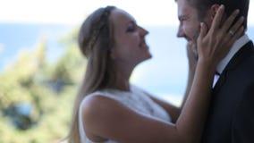 La novia y el novio en el balcón del hotel contra la perspectiva de la costa de mar almacen de metraje de vídeo