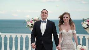 La novia y el novio en la ceremonia que se casa Un par joven en el amor que pasa a través de las huéspedes que lanzan los pétalos almacen de metraje de vídeo