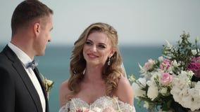 La novia y el novio en la ceremonia que se casa Un par joven en soportes del amor en el arco El casarse por el mar almacen de metraje de vídeo
