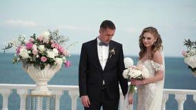 La novia y el novio en la ceremonia que se casa Un par joven en soportes del amor en el arco El casarse por el mar almacen de video