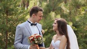La novia y el novio en el novio del bosque con un ramo de la novia La novia vuelve al novio y cierra el suyo almacen de video
