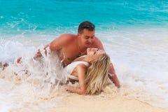 La novia y el novio en la playa tropical apuntalan en la onda Foto de archivo