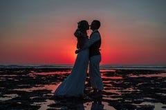 La novia y el novio en la puesta del sol imagen de archivo