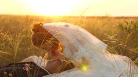 La novia y el novio en la puesta del sol están descansando juntos sentarse en campo con trigo y la sonrisa en uno a honeymoon ama metrajes