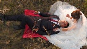 La novia y el novio en la puesta del sol están descansando juntos sentarse en campo con trigo y la sonrisa en uno a honeymoon ama almacen de video