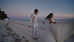 La novia y el novio en la puesta del sol en una playa tropical hermosa La novia sensual baila antes del novio, aferrándose a almacen de metraje de vídeo