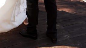 La novia y el novio en trajes festivos se están colocando en un embarcadero de madera almacen de video