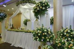 La novia y el novio en una tabla del restaurante adornada con las flores Fotografía de archivo libre de regalías