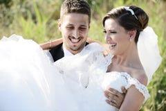 La novia y el novio en una tenencia ligera hermosa abrazan foto de archivo libre de regalías