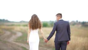 La novia y el novio están caminando a lo largo de la trayectoria en el campo almacen de metraje de vídeo