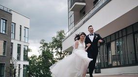 La novia y el novio están corriendo alrededor de la sonrisa de la ciudad plan hermoso en la cámara lenta Amor y familia almacen de video