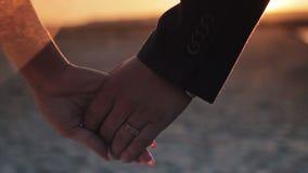 La novia y el novio están llevando a cabo las manos en la playa