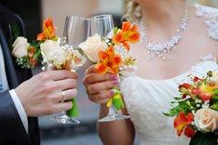 La novia y el novio están sosteniendo los vidrios del champán Foto de archivo