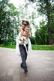 La novia y el novio felices en la boda recorren en el parque Fotos de archivo libres de regalías