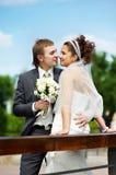 La novia y el novio felices en la boda recorren en el parque Imagen de archivo libre de regalías