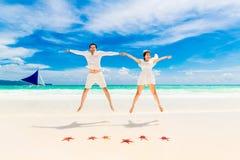 La novia y el novio felices en la playa tropical apuntalan con las estrellas de mar rojas Imagen de archivo