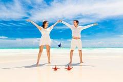 La novia y el novio felices en la playa tropical apuntalan con las estrellas de mar rojas Fotografía de archivo libre de regalías