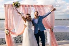 La novia y el novio felices se colocan en el embarcadero debajo del arco de la boda imágenes de archivo libres de regalías