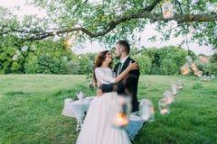La novia y el novio hermosos por la tarde parquean el abarcamiento debajo del árbol adornado con muchas linternas Fotografía de archivo libre de regalías