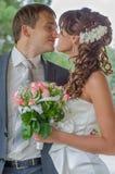 La novia y el novio jovenes felices abrazan y se besan Imagenes de archivo