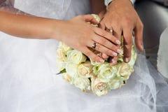 La novia y el novio llevan a cabo las manos con los anillos de bodas de oro sobre weddi Imagenes de archivo