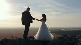 La novia y el novio llevan a cabo las manos en las montañas oscilan en la puesta del sol almacen de video