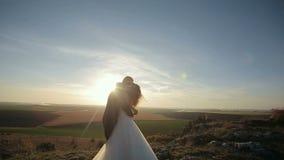 La novia y el novio llevan a cabo las manos y el funcionamiento a lo largo de las montañas oscila en la puesta del sol metrajes