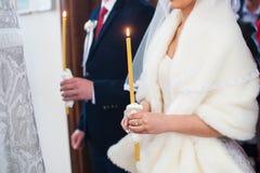 La novia y el novio llevan a cabo velas en iglesia en la boda fotografía de archivo libre de regalías