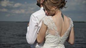 La novia y el novio que abrazan encariñado cerca de un lago almacen de metraje de vídeo