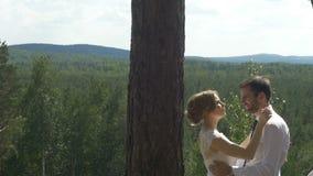 La novia y el novio que abrazan encariñado en el parque almacen de video