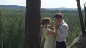 La novia y el novio que abrazan encariñado en el parque almacen de metraje de vídeo