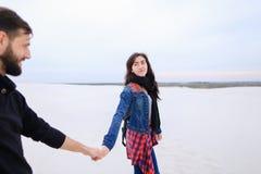 la novia y el novio que caminan en la playa buscan el lugar f Foto de archivo