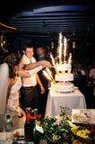 La novia y el novio que cortan la torta en la ceremonia de la celebración Imagenes de archivo