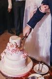 La novia y el novio que cortan el pastel de bodas delicioso con las rosas en se casan Fotos de archivo libres de regalías