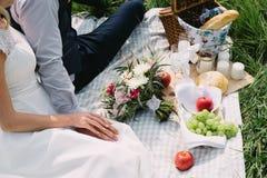La novia y el novio que llevan a cabo las manos en comida campestre de la boda en el verano imagen de archivo