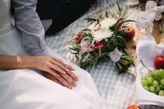 La novia y el novio que llevan a cabo las manos en una comida campestre El ramo, fruta, mira al trasluz la mentira en la manta Imagen de archivo libre de regalías