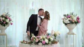 La novia y el novio que se besan en el banquete que se casa Pares que se casan cariñosos jovenes en tienda almacen de video