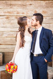 La novia y el novio que se besan encendido wodden el fondo Fotografía de archivo