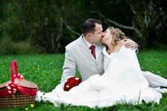 La novia y el novio románticos del beso en la boda meriendan en el campo Foto de archivo