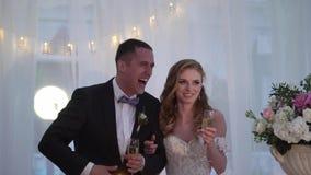 La novia y el novio se divierten en el banquete que se casa Pares que se casan cariñosos jovenes en tienda almacen de video