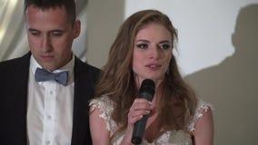 La novia y el novio se divierten en el banquete que se casa Pares que se casan cariñosos jovenes en tienda metrajes