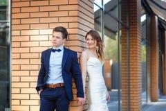 La novia y el novio se están colocando en la esquina de la casa y del control fotografía de archivo
