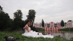 La novia y el novio se están sentando en hierba en el parque metrajes