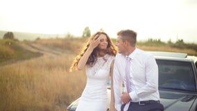 La novia y el novio se están sentando en la capilla del coche en el campo metrajes