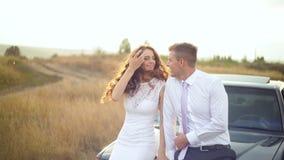 La novia y el novio se están sentando en la capilla del coche en el campo almacen de video