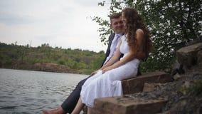 La novia y el novio se están sentando en la orilla del lago almacen de metraje de vídeo