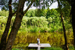 La novia y el novio se están colocando en un embarcadero de madera cerca de la charca Foto de archivo libre de regalías